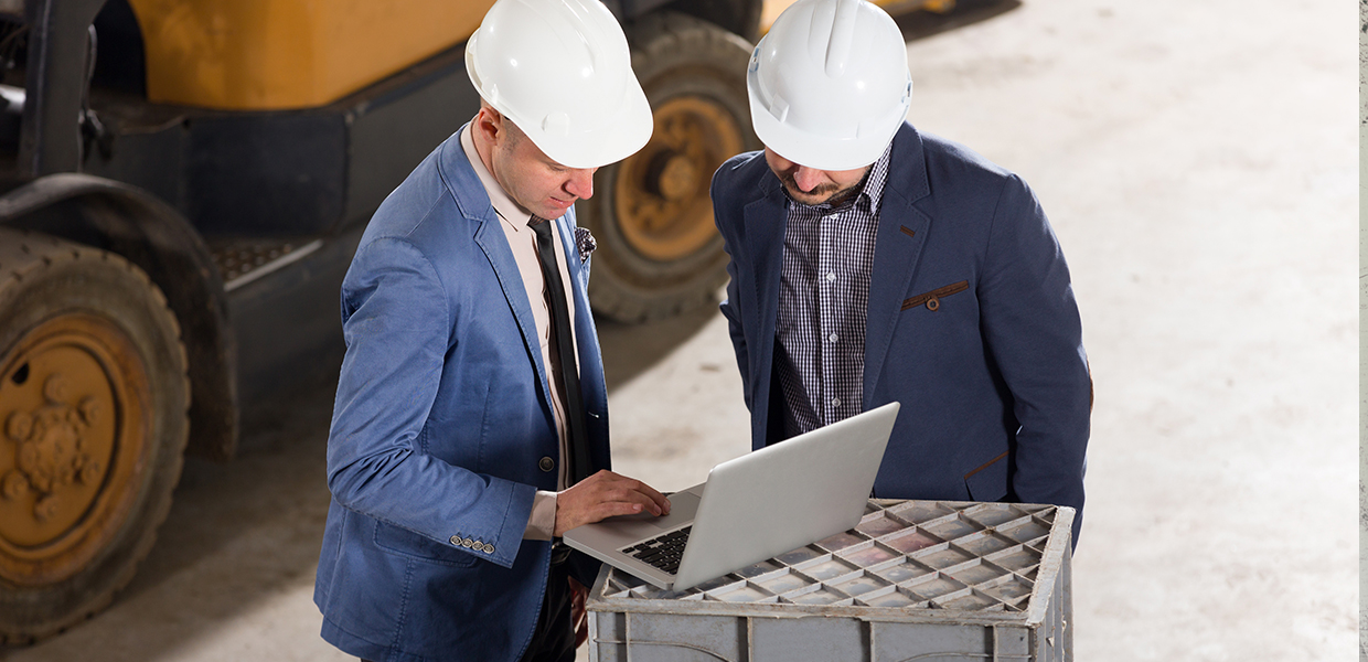 Business men in front of forklift looking at a laptop